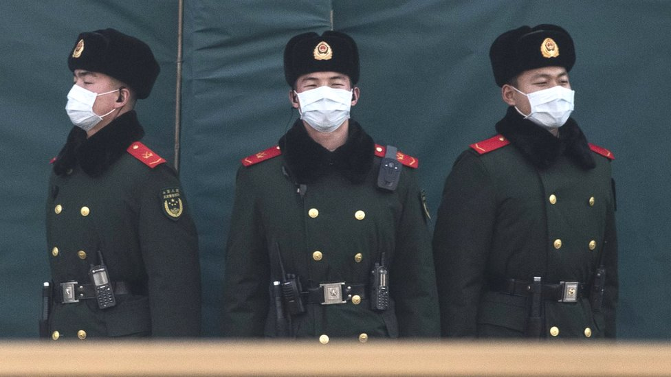 Chinese policemen wearing masks