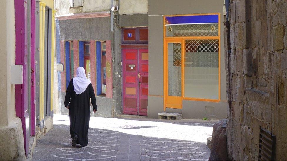 امرأة مسلمة تمشي في شارع ضيق في لوديف، وهي بلدة في هيرو في جنوب فرنسا