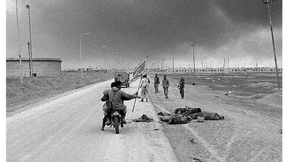 جنود ايرانيون على دراجة نارية يمرون بجانب جثث جنود عراقيين