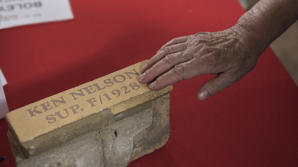 Hand touching brick labelled Ken Nelson