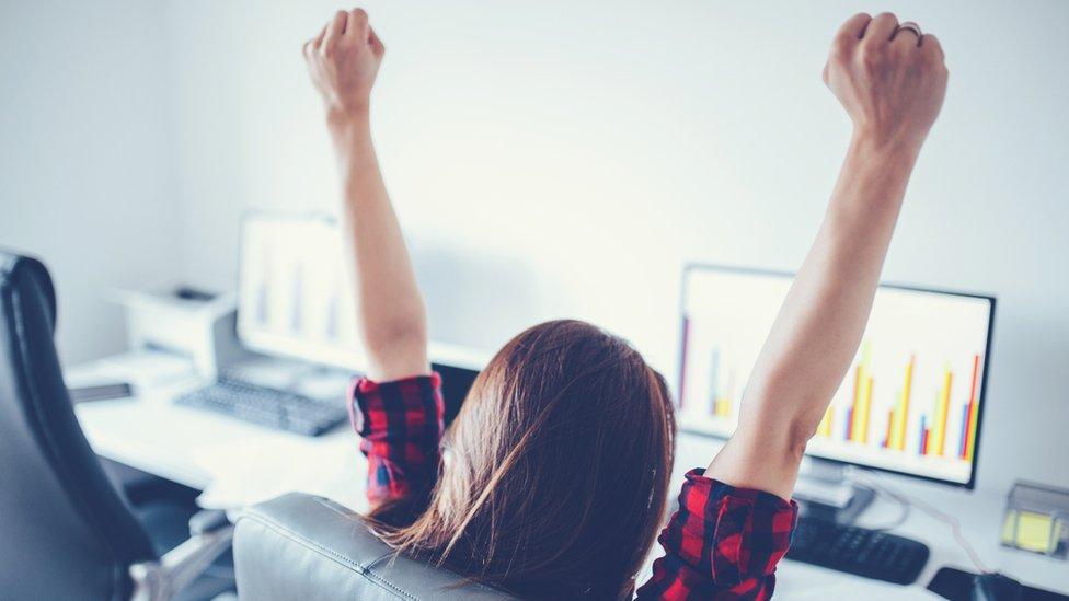 Una empleada con los brazos alzados.