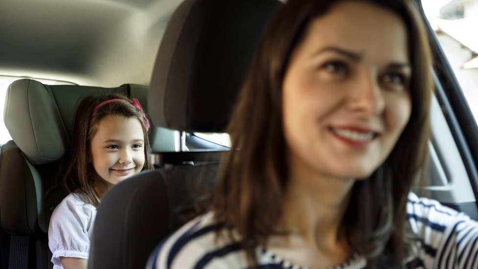 Woman driving with a child in the back seat