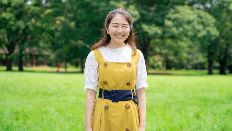 Momoko Nojo, Japanese woman stands in front of trees wearing yellow dress