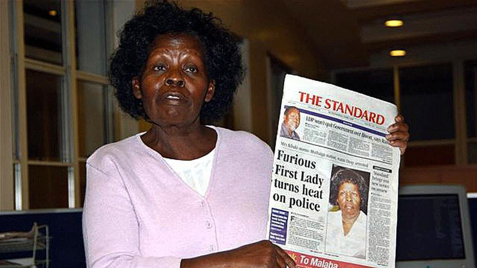 Kenya's First Lady Lucy Kibaki speaks to the media while holding a copy of a local newspaper with the headline 'Furious First Lady turns heat on police' at Nation Media Centre in downtown Nairobi early 03 May 2005. The First Lady, irritated by stories published in the local media about her family, stormed the newspaper offices late 02 May where she held a marathon press conference lasting until nearly 5am in the morning