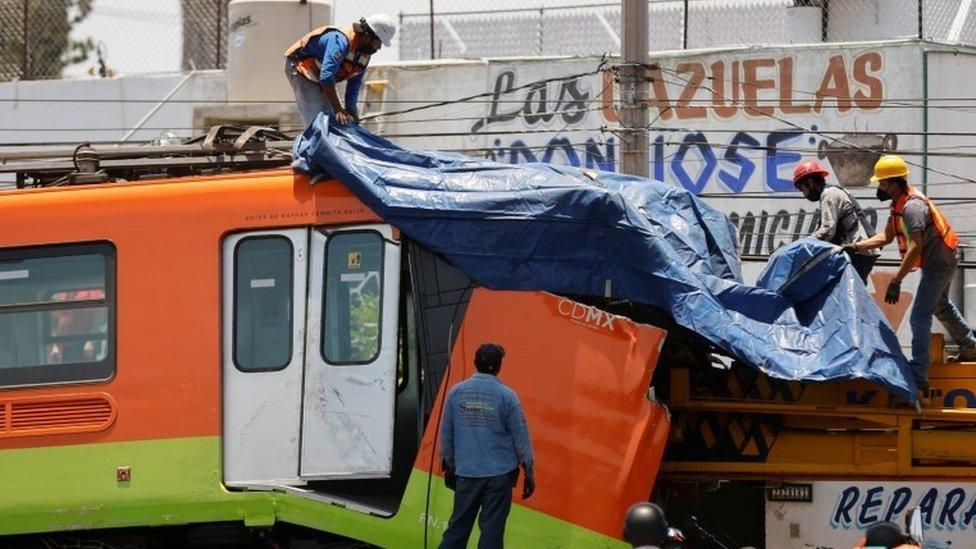 عمال يغطّون عربة قطار متضررة بعد نقلها من موقع الانهيار