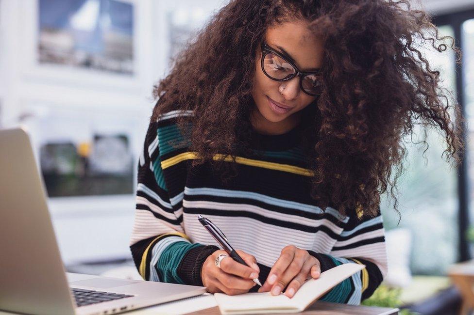 Una mujer escribe en un cuaderno.