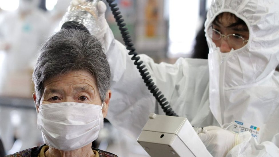 Trabajadora midiendo la radioactividad en una mujer luego del accidente en la planta nuclear en Fukushima