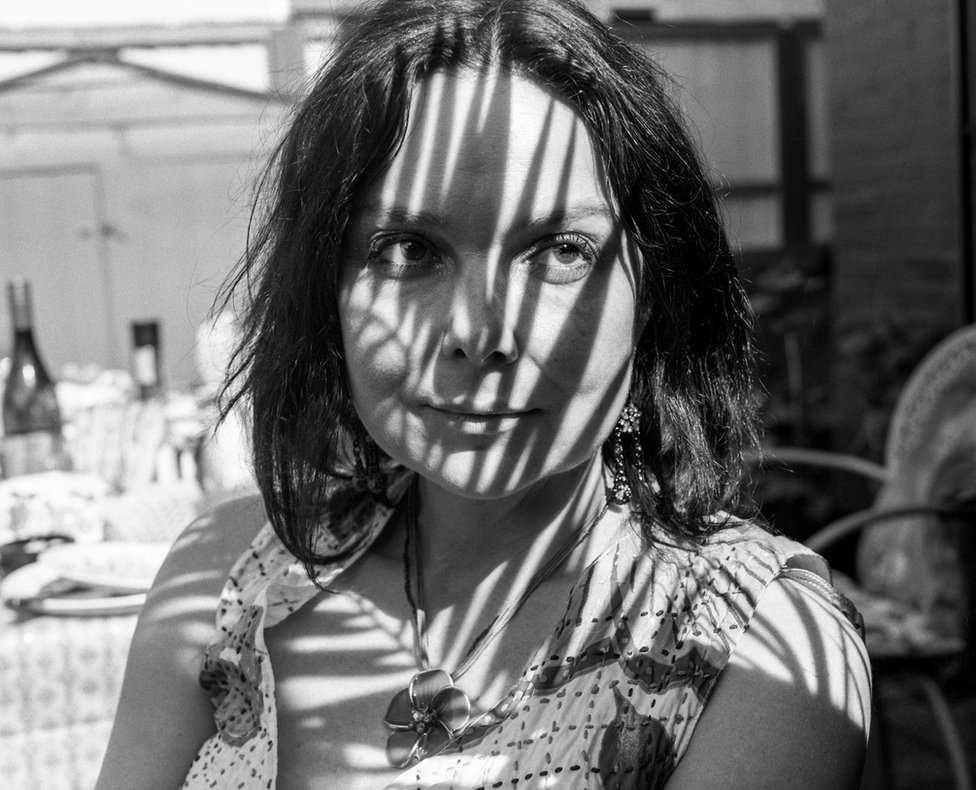 A portrait of a woman with light and shadows cast on her face