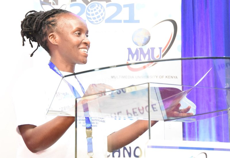 Dr Gladys Nyachieo standing at a lectern at a Multimedia University event.