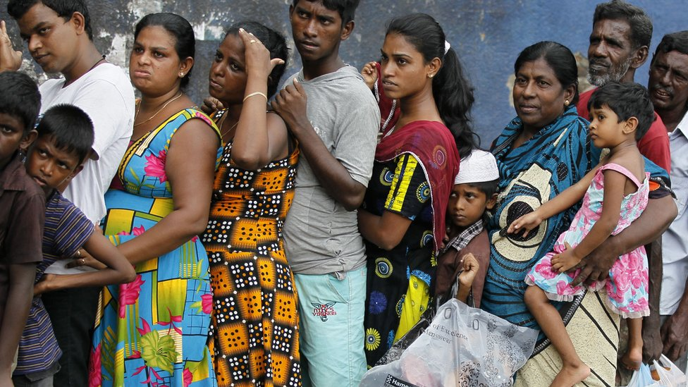 Sri Lankan flood victims line up to receive relief materials in a flood affected area near Colombo