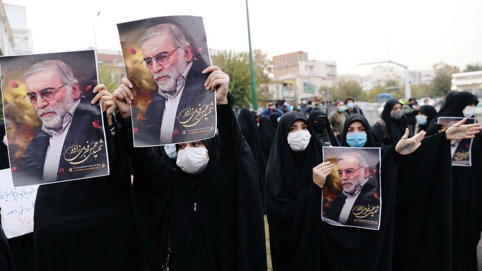 -Mujeres cubiertas con mascarillas sostienen carteles con la imagen de Mohsen Fakhrizadeh en Teherán, Irán