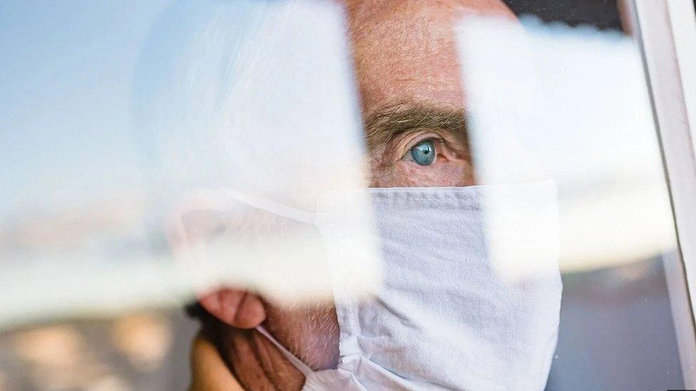 Homem de máscara olha pela janela