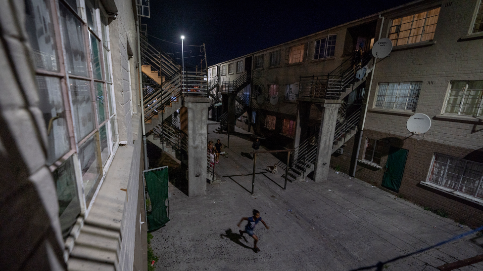 A boy running between apartments in Manenberg, Cape Town - South Africa