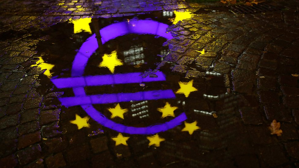 The euro sign in front of the former headquarters of the European Central Bank (ECB) is reflected in a puddle during heavy rain in Frankfurt