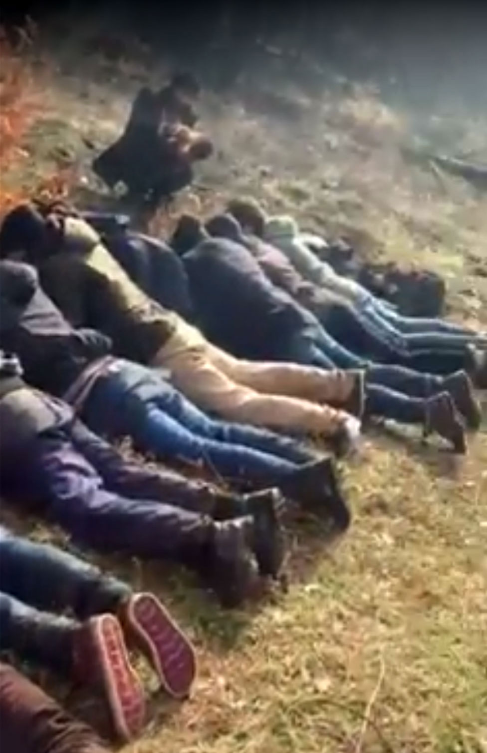 Migrants forced to lie on the ground