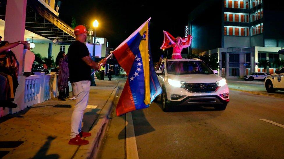 Un hombre sostiene una bandera venezolana en Florida.