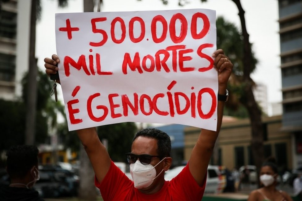 A man holds up a sign protesting against the Covid death toll in Brazil