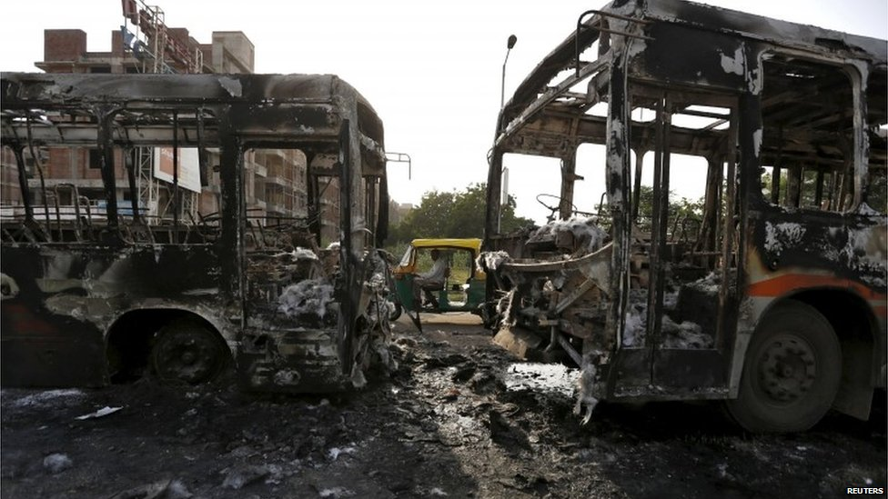 An auto rickshaw moves past damaged passenger buses which were burnt in Wednesday's clashes between protesters and police in Ahmedabad, India, August 27, 2015