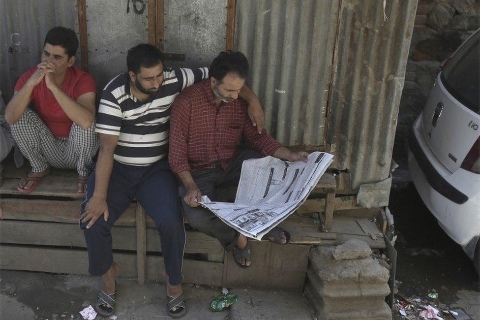 Kashmiri men read the newspaper during a curfew in Srinagar, Indian controlled Kashmir, Thursday, Aug. 18, 2016.