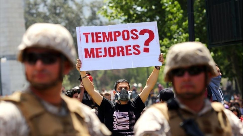 """A demonstrator holds a sign that reads """"Better times?"""" as soldiers stand guard at Plaza Italia square in Santiago, Chile, on October 21, 2019."""