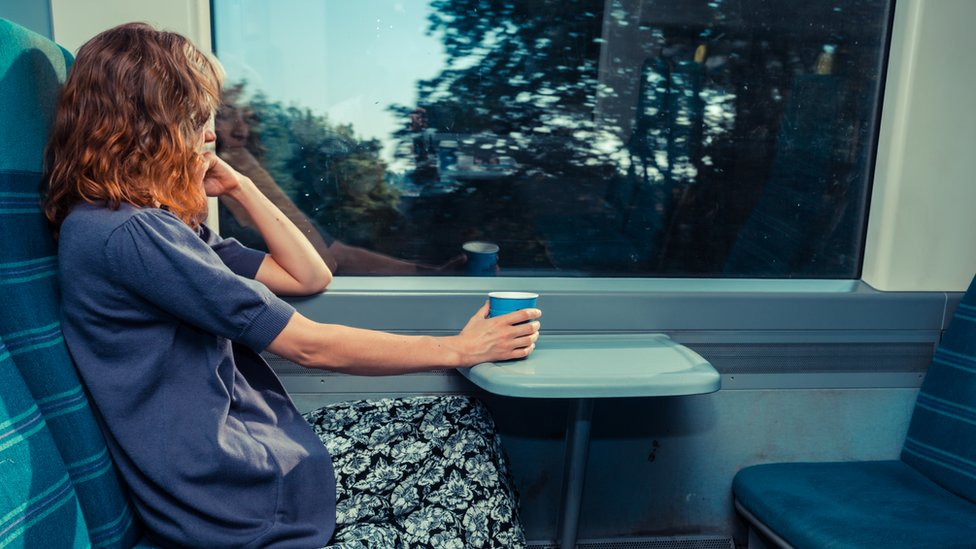 Model posed photo of woman staring out of a train carriage window