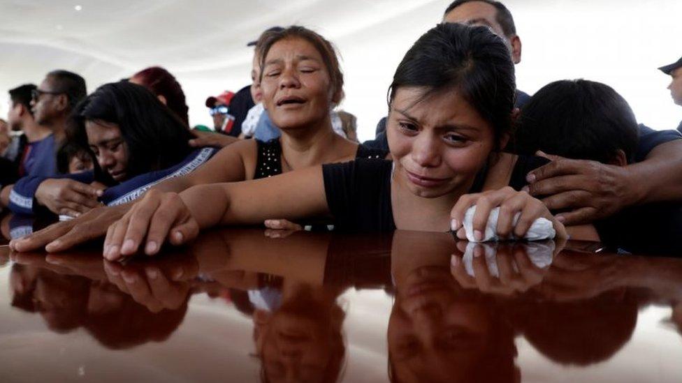 Personas lloran junto a un ataúd