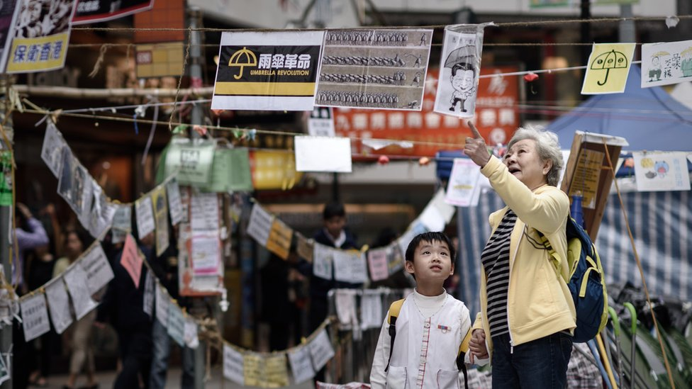 A elderly woman explains to a child the meaning of posters set up by pro-democracy protesters at a protest site in the Causeway Bay district of Hong Kong on November 14, 2014.