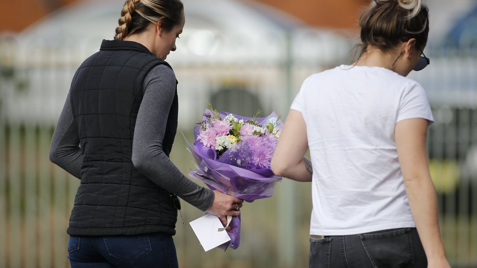 Two women bring flowers and a card to the scene of the fire