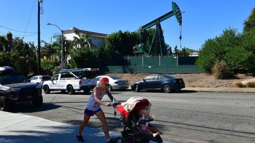 Una mujer camina con su bebé por una calle residencial de Los Ángeles y al fondo se ve un aparato extractor de petróleo.