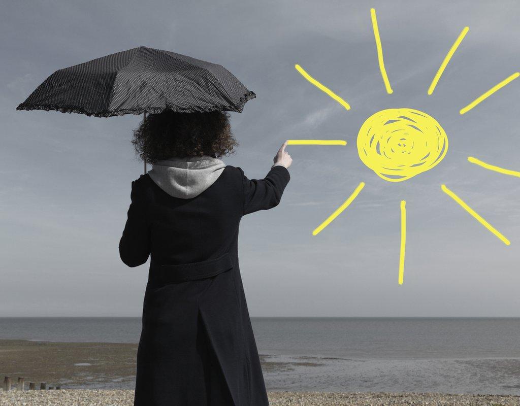 Niña pintando un sol en un cielo gris