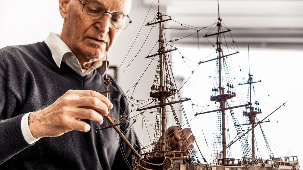 Un hombre de edad armando un modelo de barco