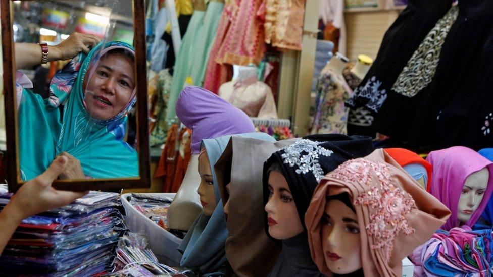 A woman shops for headscarves ahead of Eid al-Fitr in Jakarta, Indonesia