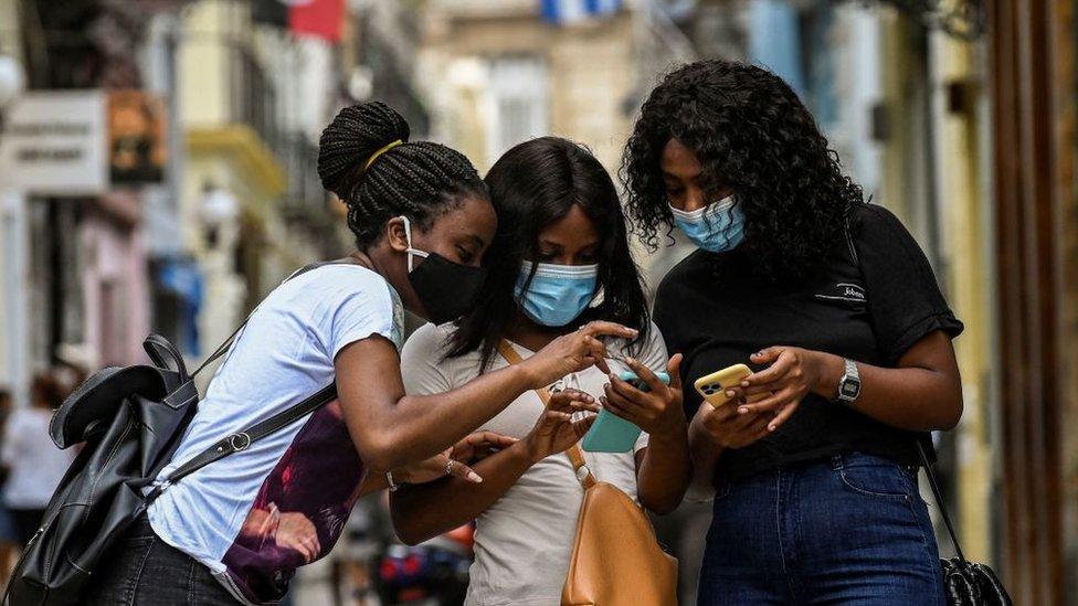 Jóvenes comprueban sus celulares en Cuba