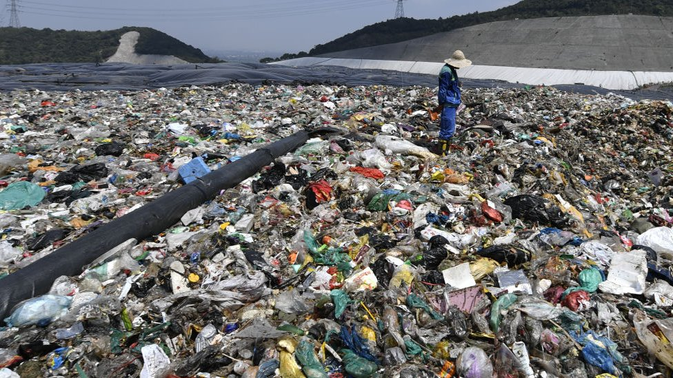 A worker prepares to cover the waste with a capping layer at the Tianziling landfill site on August 7, 2019 in Hangzhou