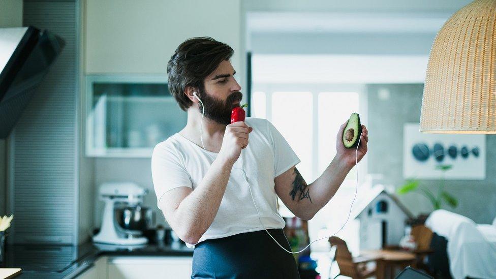 Un hombres canta en la cocina usando un pimiento como micrófono.