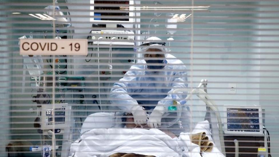 Por trás de persiana em hospital, profissional manipula paciente em maca