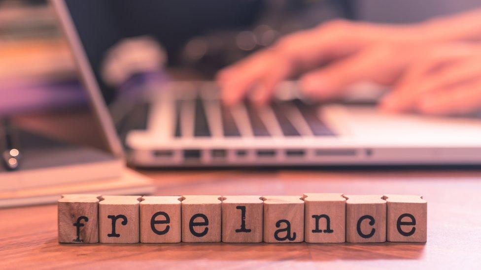 Letrero de freelance frente a una computadora.