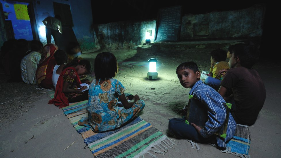 Children studying by solar light at a night school in Ajmer, Rajasthan