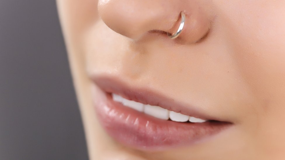 Plano corto de una mujer con un piercing en la nariz.