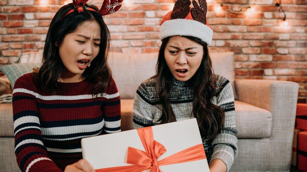 Dos chicas decepcionadas ante el contenido de una caja.