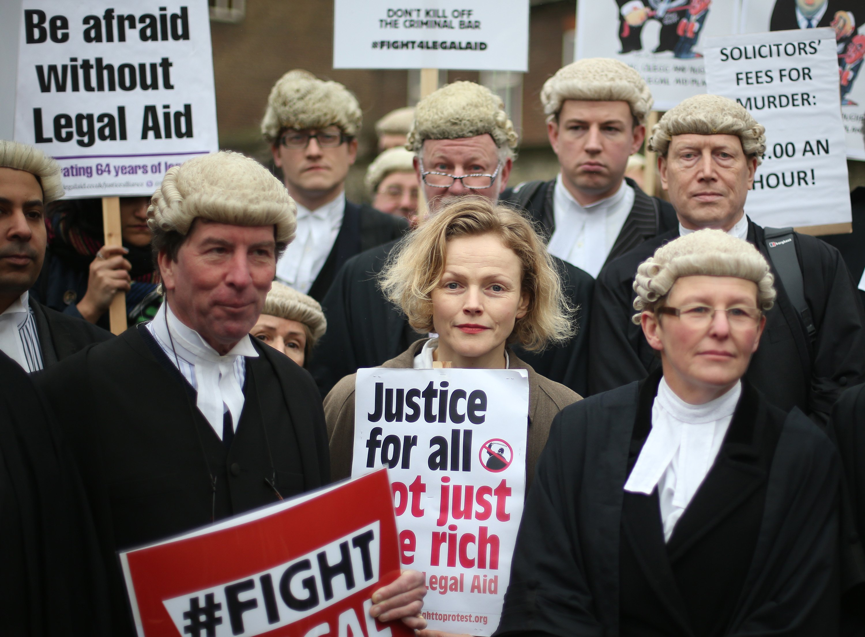 legal aid protest actress maxine peake with barristers in wigs and gowns. sign reads justice for all, not just the rich