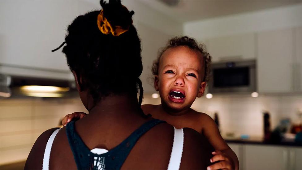 Una madre sostiene a un niño que llora