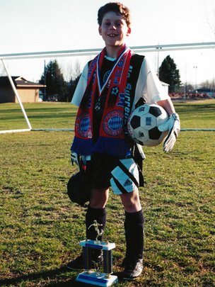 Adam Maier-Clayton as a child, posing with soccer trophies