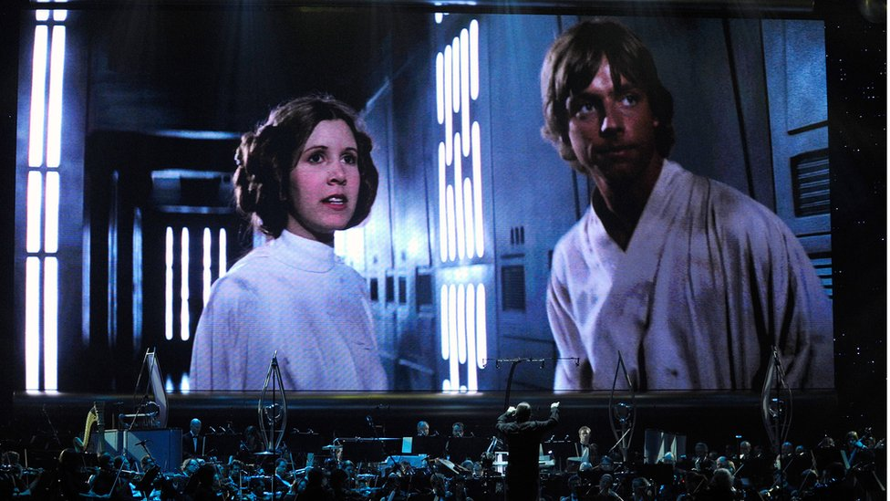 Actress Carrie Fisher's Princess Leia Organa character and actor Mark Hamill's Luke Skywalker character from 'Star Wars Episode IV: A New Hope' are shown on screen while musicians perform during 'Star Wars: In Concert' at the Orleans Arena May 29, 2010 in Las Vegas, Nevada.