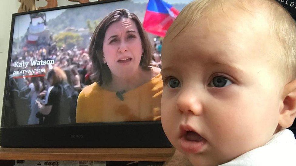 Bebé Isadora con mamá Katy Watson en la televisión detrás de ella
