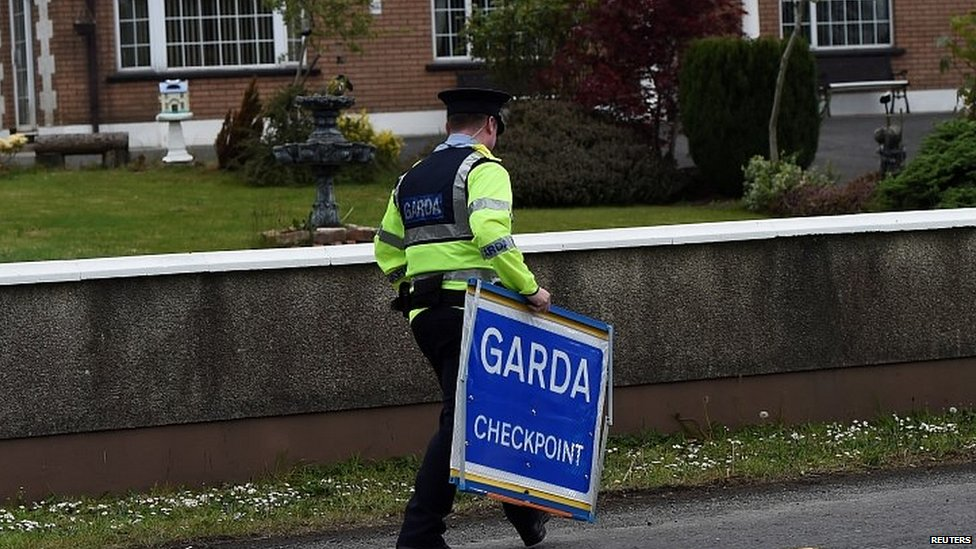 An Irish police officer removes a Garda checkpoint sign at the Armagh and County Louth border between Northern Ireland and Ireland, during a visit by European Union Chief Negotiator for Brexit Michel Barnier
