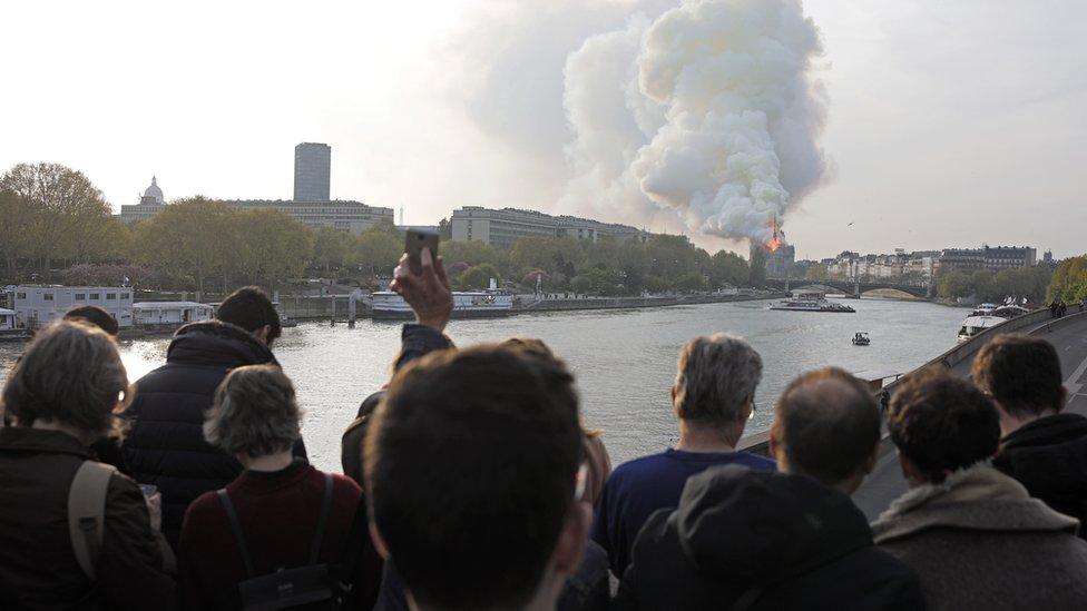 Personas observan el incendio de la catedral de Notre Dame