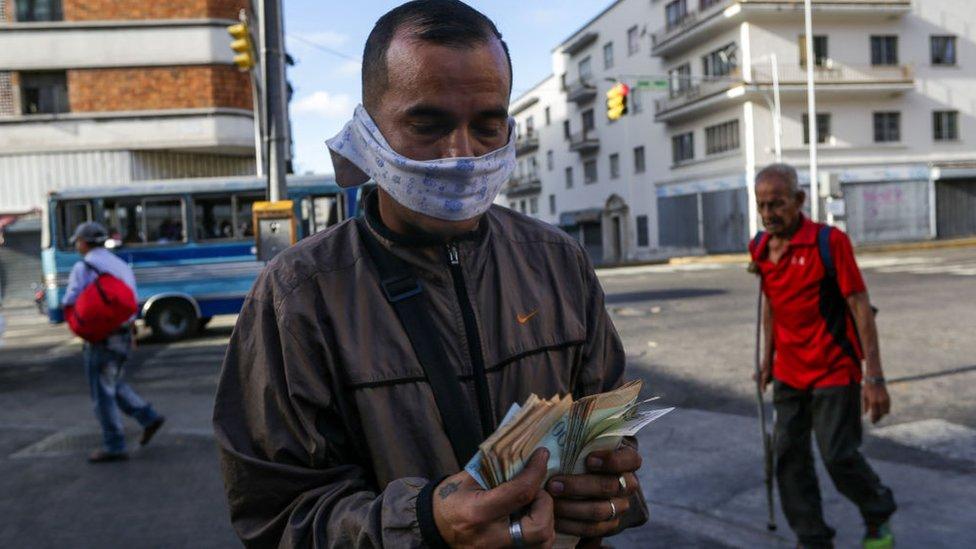 Un hombre contando un fajo de billetes con una mascarilla de tela.