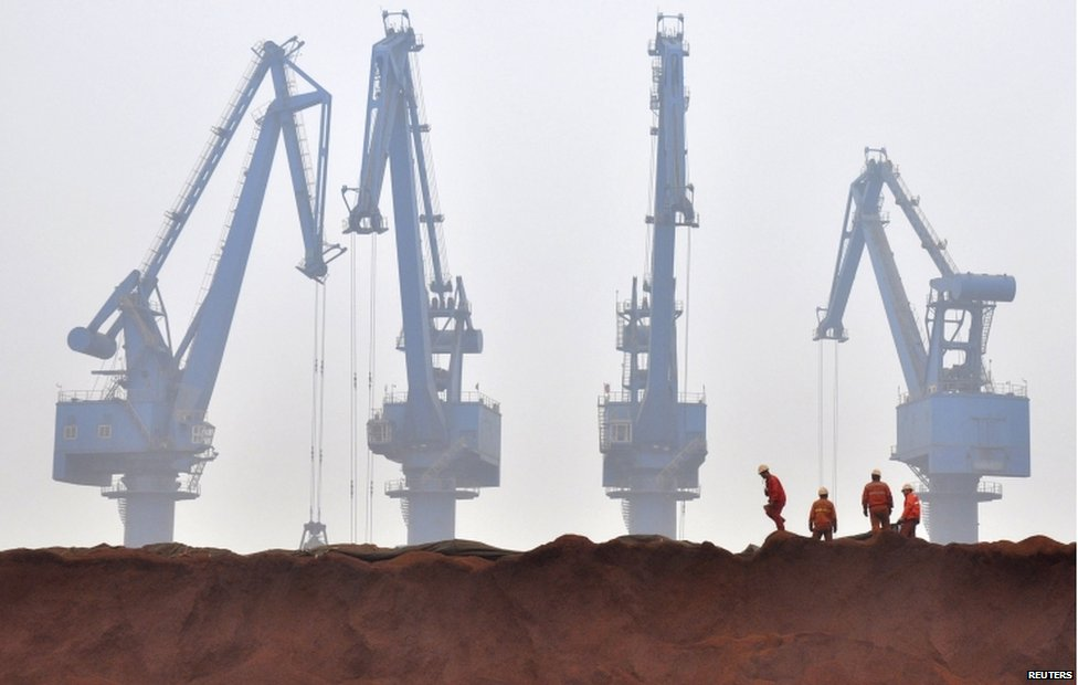 Workers remove the cloth covering iron ore waiting to be transported at a port in Tianjin municipality in this 29 March 2010 file picture