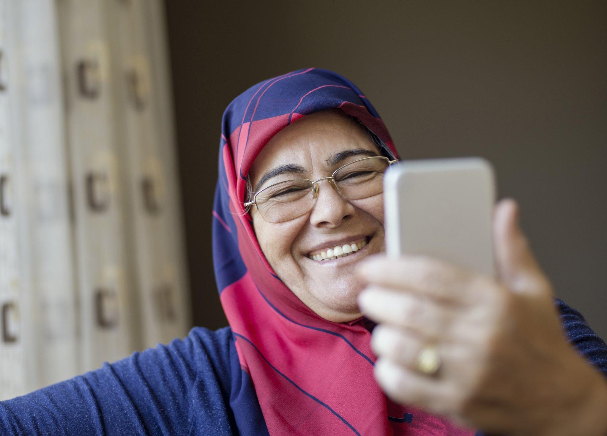 صورة تعبيرية لامرأة تتحدث مكالمة فيديو عبر هاتفها المحمول